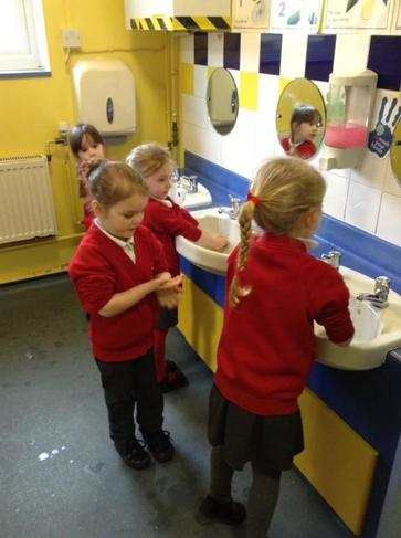 Practising washing hands to remove germs.