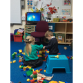Two friends working together to build a tall tower