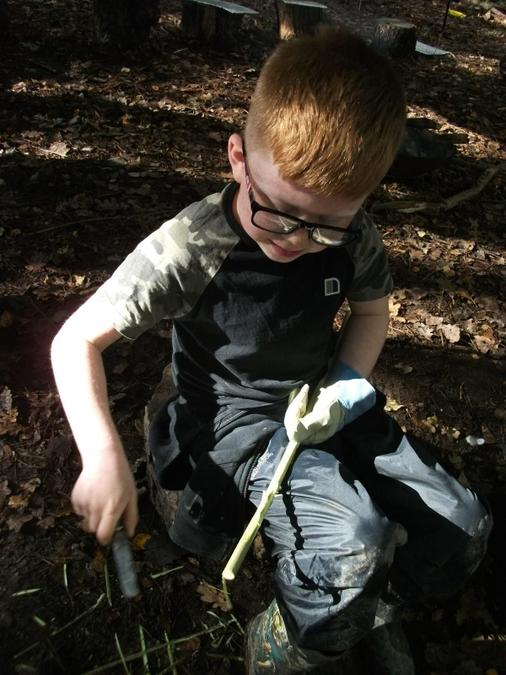 Using a knife to strip bark from willow