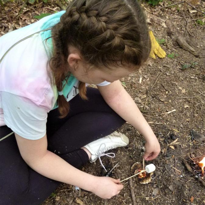 Toasting a marshmallow over their own mini-fire