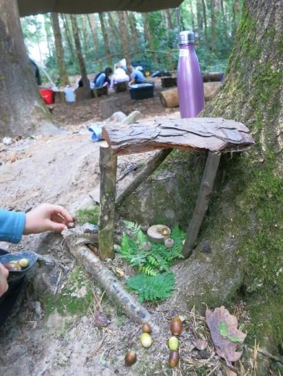 Finishing touches to tree root fairy house