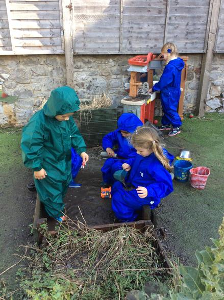 Playing in the mud kitchen.