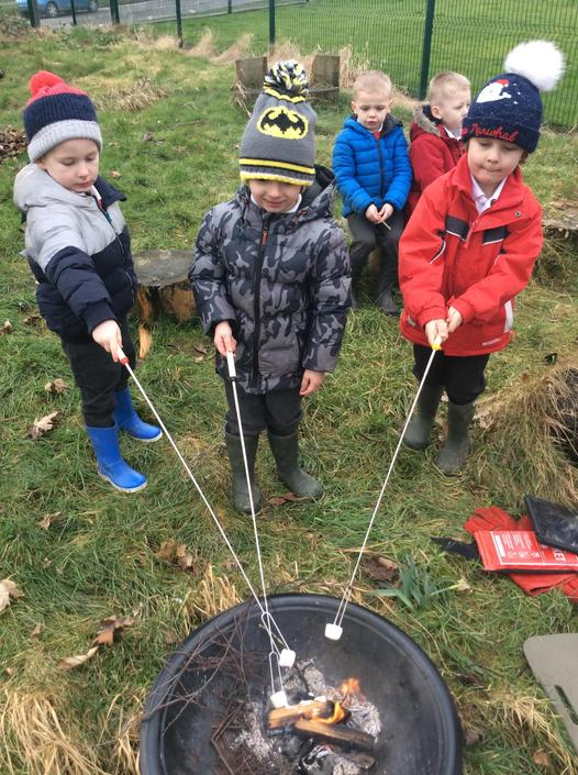 Toasting marshmallows in our Forest Schools area.
