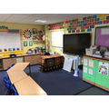Interactive whiteboard/TV and Mrs. King's desk. Our RE and Christian Values display area.