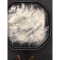 Making marks in a glittery flour tray using sticks and fingers.
