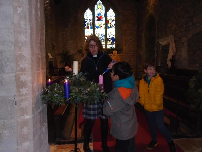Carefully lighting then next candle in the Advent ring.