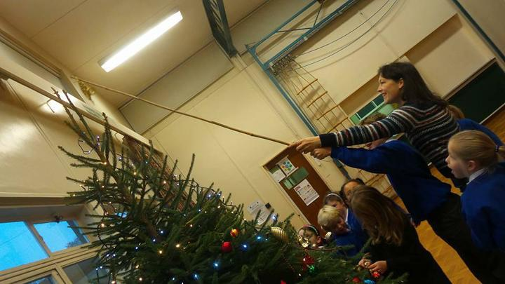 Our Chairperson puts the star on top of the tree!