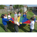 Green team play parachute games together.