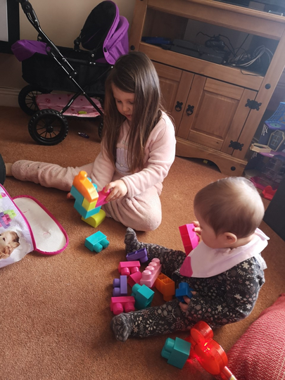Building blocks with her little sister.