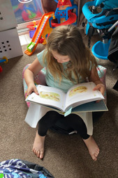 Reading to her little brother