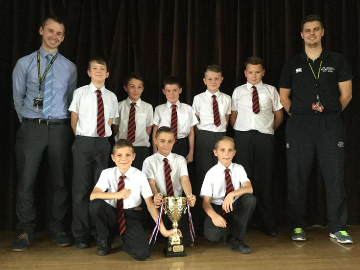 Triumphant team sharing the cup with the school.