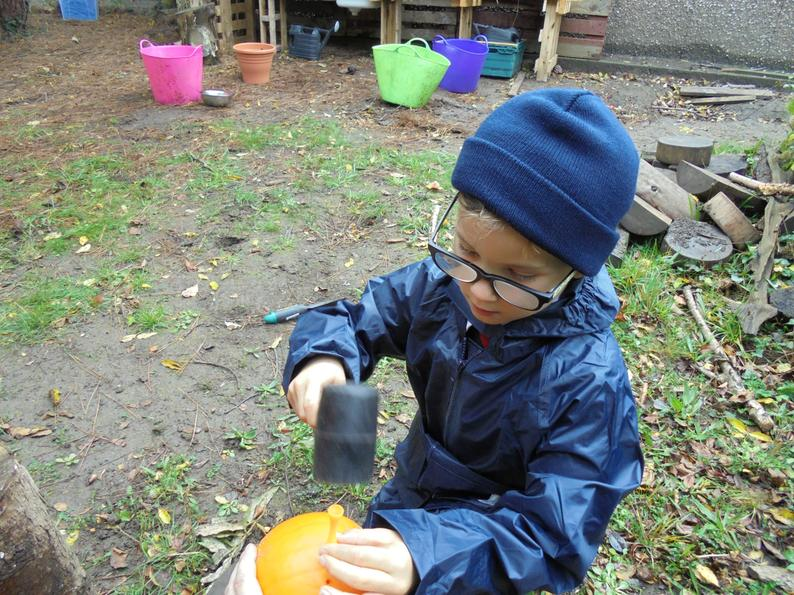Using a hammer to make holes in a pumpkin