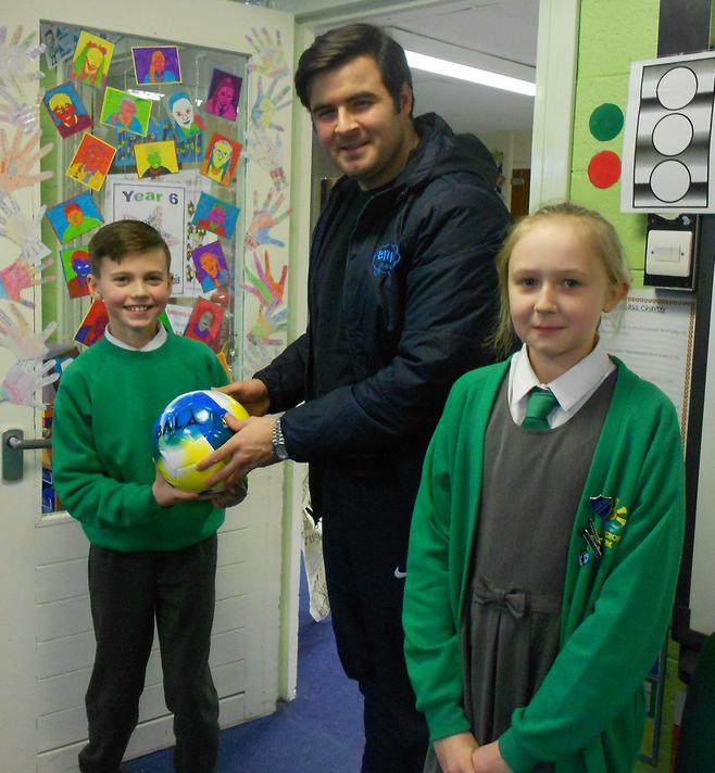 Presenting a football to John McBride - Enrich