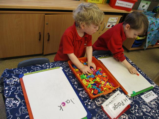 Forming our name with magnetic letters.