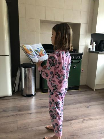 Nicole is busy reading in her kitchen