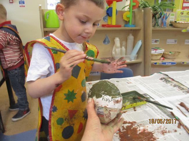 Carefully painting the dinosaur egg.