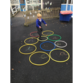B, playing a letter recognition hoop game