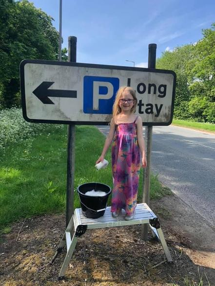 Lily cleaning street signs, supporting the local community