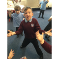 Acting out 'Old Bear' - holding up heavy bricks.