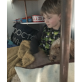 Solly listening to his teacher's stories in a cosy den.