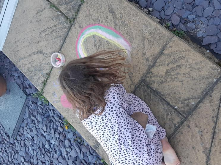 Sophia drawing a rainbow outside her house