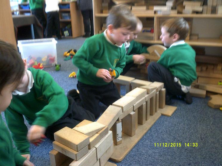We carefully join construction pieces together.