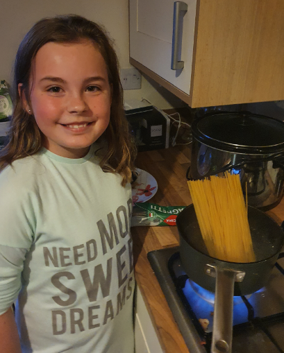 Ava cooking her family Spaghetti Bolognese.