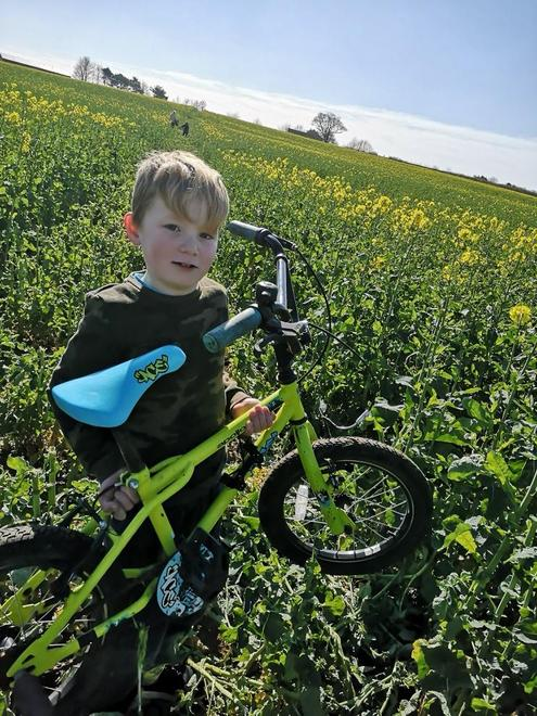 Weight lifting his bike through a field!