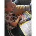 Reading a wrestling magazine.