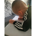Concentrating on his writing.