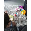 Poppy reading to her teddies.