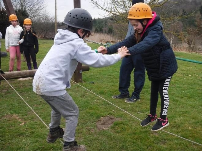 Year 5 help each other on the assault course.