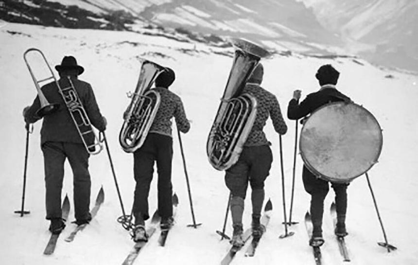Skiers with instruments on their backs
