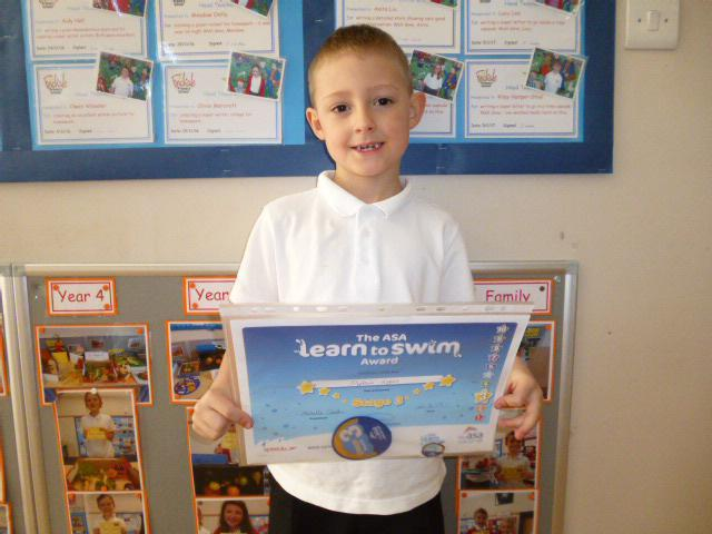 Dylan Y1 with his swimming award.