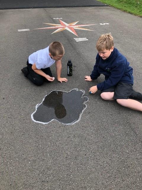 Drawing round the puddles with chalk so we can observe what happens throughout the day.