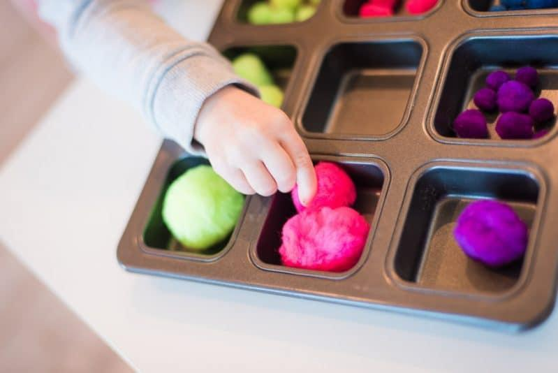 Sort pom poms into different slots in cake baking trays or other things..