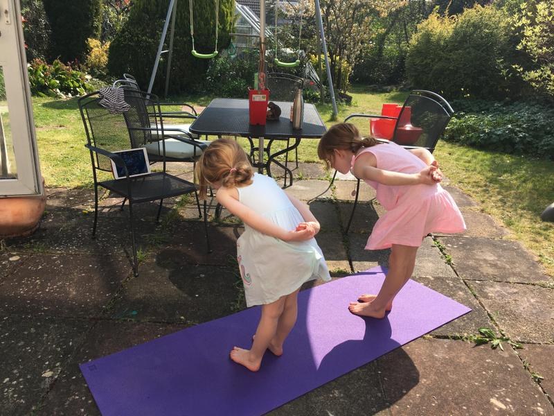 Anna and her sister do yoga in the sun