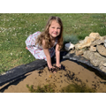 Evie checking out the tadpoles in her pond