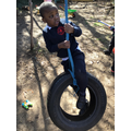 Climbing up onto the tyre swing using whole body strength and perseverance.