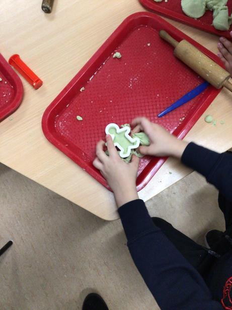 Using the playdough cutters to help us create playdough babies.