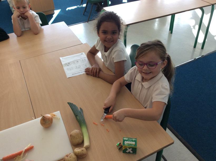 Kiera and Sophia peeling a carrot.