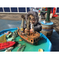 Engaging in small world play, using the ship and the ocean