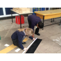 Using metre sticks to measure large objects.