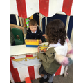 Engaging in role play and buying food from the shop.