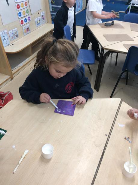 We glues gems onto felt squares