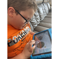 Josh is reading a dinosaur book on BugClub.