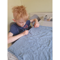 Zak has been learning how to sew.
