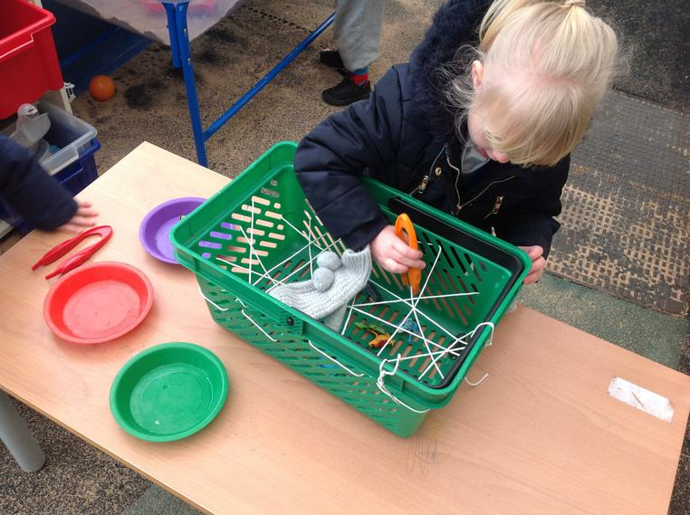 Challenging children to remove 'bugs'with tweezers