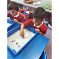 Practising letter formation in the coloured salt