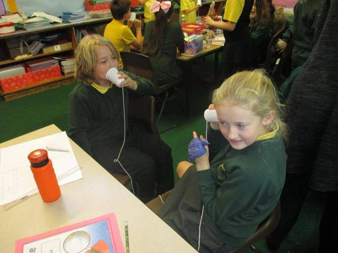 Testing their plastic cup telephone